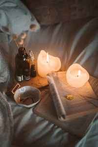 lighted candle on white book beside black glass bottle