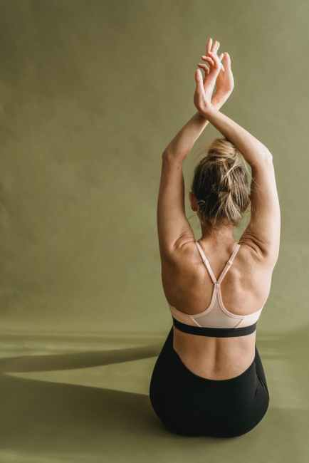 unrecognizable graceful female dancer performing movement with raised arms in studio