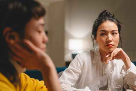 thoughtful young ethnic women having conversation at table at home