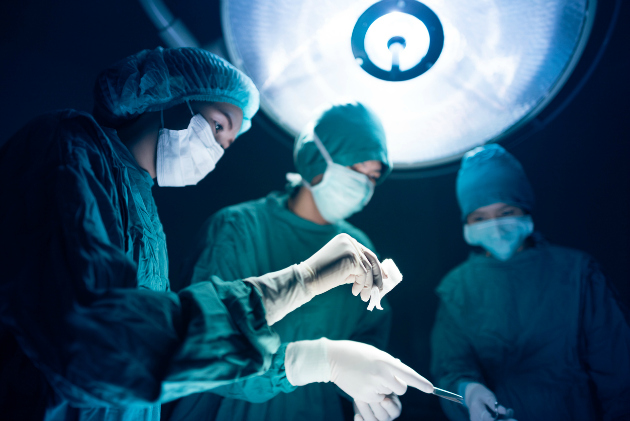 Surgeons team standing above of the patient before surgery with equipment , selective focus on hand