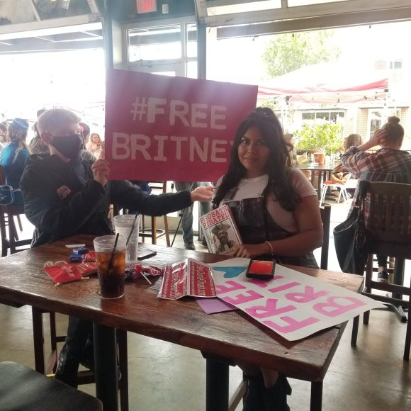 """Nov 10, 2020: San Antonio's #FreeBritney rally, to end pop singer Britney Spears' conservatorship, is joined by the #FreeCharlieThrash team, including our own Brittany Martinez-Thrash, holding a copy of guardianship reform advocate Kristy Hood's book about Bexar County, """"Probate Pirates"""""""