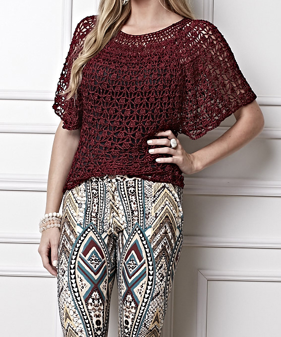 Woman dressed in a crochet blouse model bat wing in burgundy wine color, with standard and free graphic