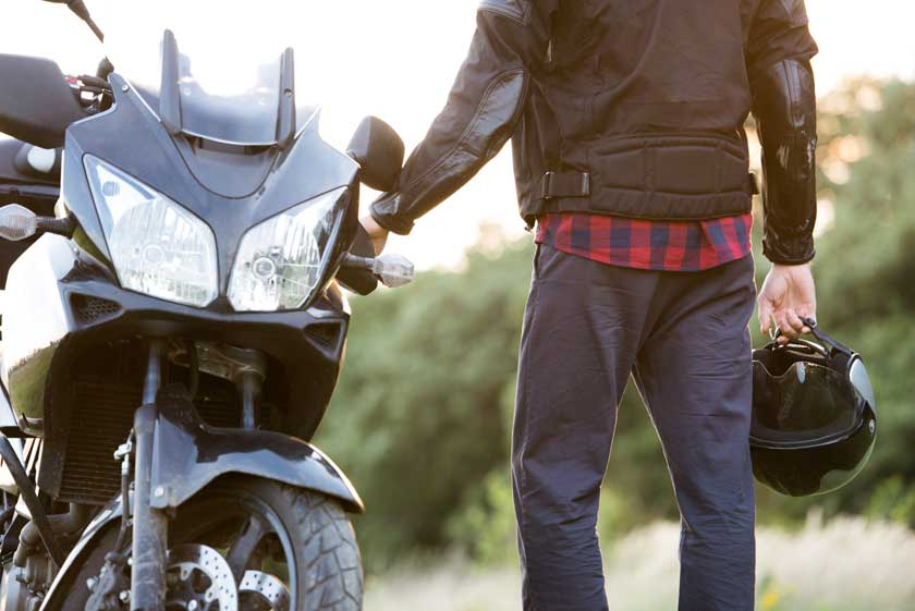 Young man standing at a motorbike