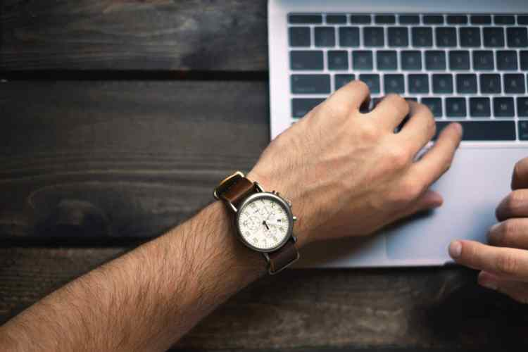 Man checking watch while on computer to understand where he spends his time