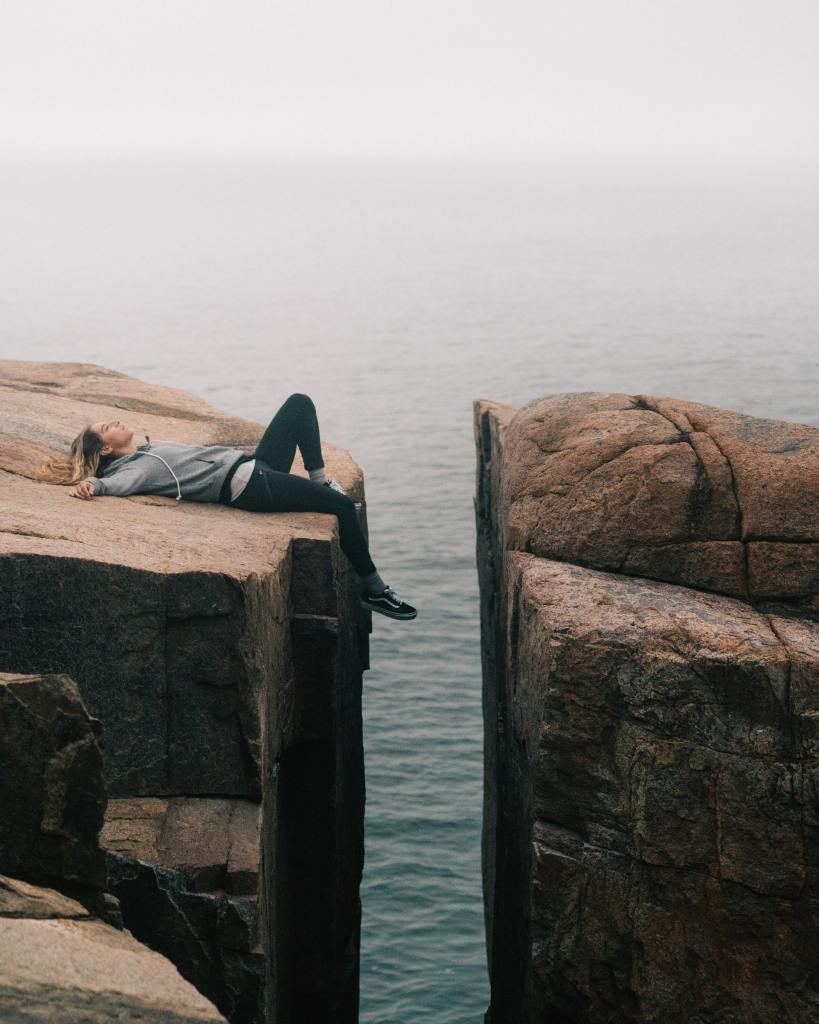 feeling unmotivated - woman laying on edge of cliff unable to bridge the gap