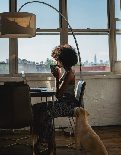 woman working with coffee while dog watches
