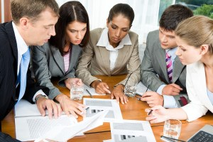 Image of five people looking at business-plan and brainstorming