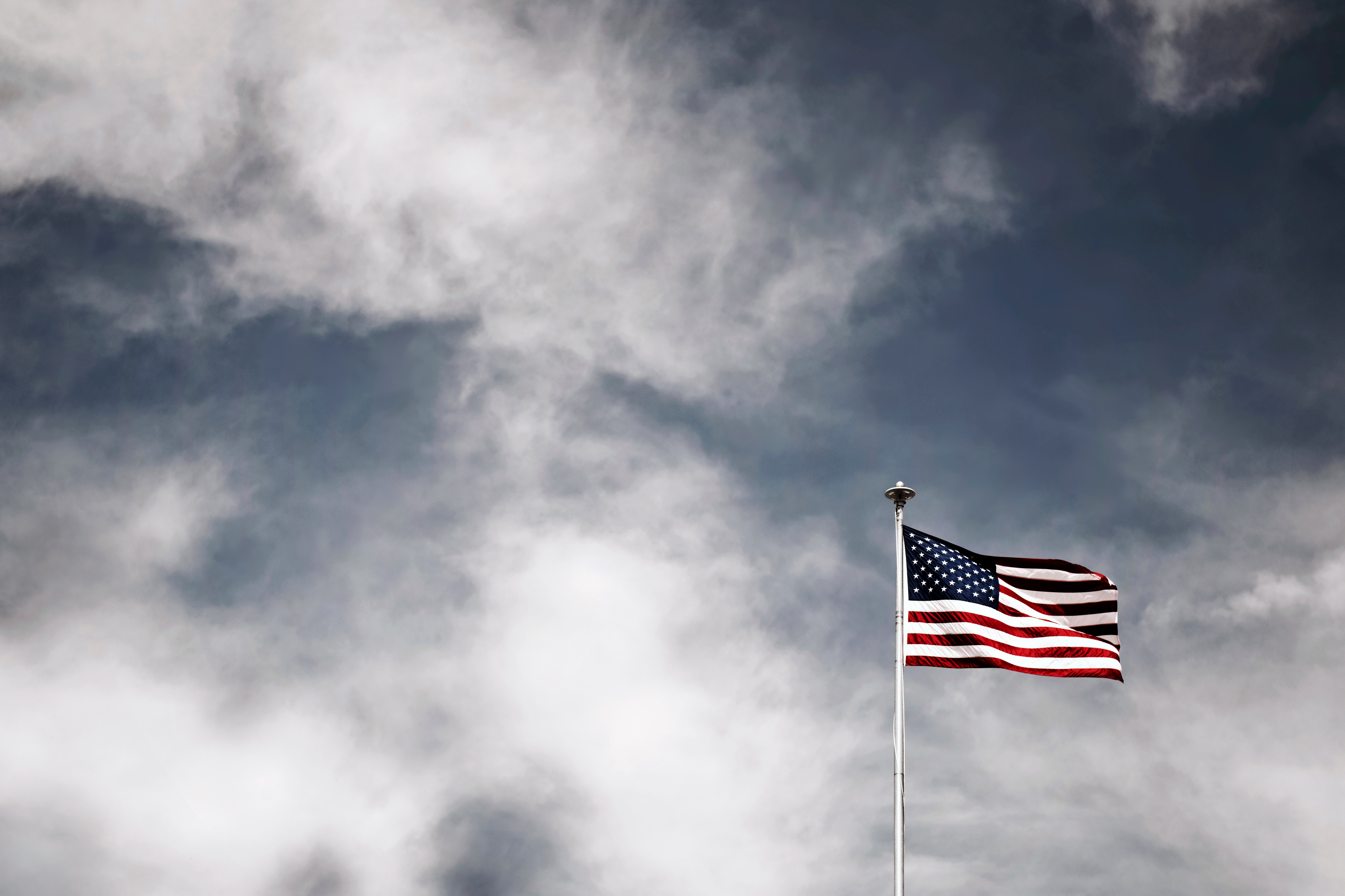 The American Flag blowing in the wind with a background of clouds.