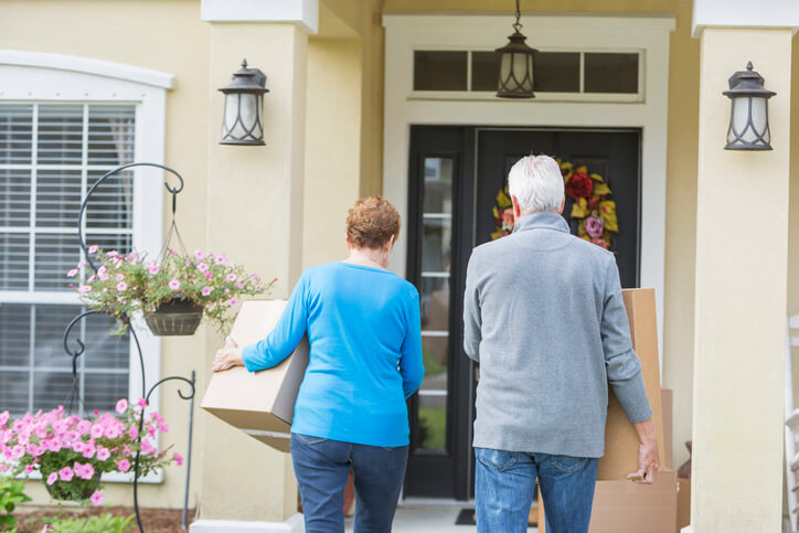 Senior couple carrying boxes and making the decision to downsize to save their retirement.
