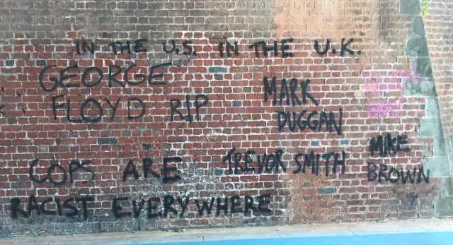 "A brick wall in Bristol. On the wall is some graffiti rendered in black spray paint: ""In the US, in the UK, the police are racist everywhere: George Floyd RIP. Mark Duggan. Trevor Smith. Mike Brown"""