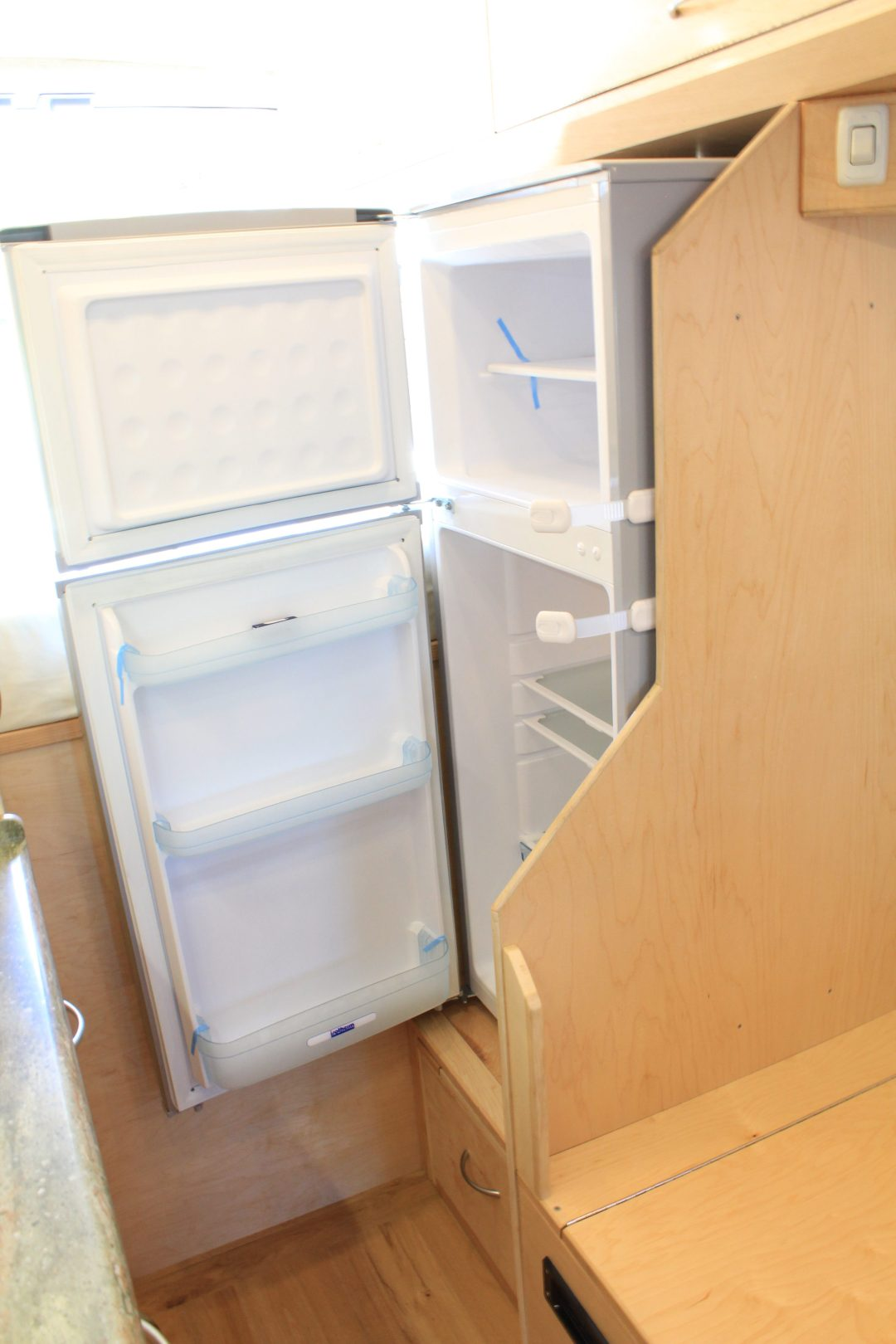 Fridge, opened, with latches to prevent opening while driving