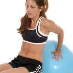 A woman using an abdominall ball.
