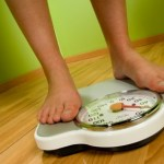 A person weighing themselves on a pair of weighing scales.