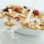 A bowl of fruit and muesli being splashed with milk.