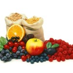 2 large sacks of cereal behind a selection of fruit.