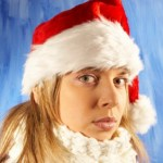 A girl in a Santa hat looking sad.
