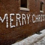 Merry Christmas written in snow on a brick wall.
