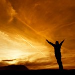 A man standing looking at a sunset with his arms outstretched.