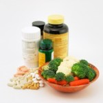 A selection of vitamin pills and bottles next to a bowl of fresh vegetables.