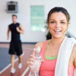 A woman in the gym drinking a bottle of water.