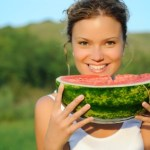 A woman eating a melon in a field.