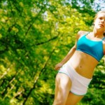A woman jogging in a sunny forest.