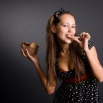 A woman eating a handful of cookies.