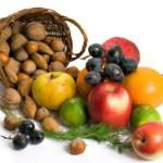 A basket of nuts next to a pile of fruit on a white background.