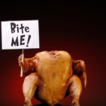"A cooked turkey holding a sign saying ""Bite Me!"""