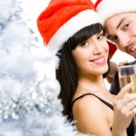 A couple in Christmas hats enjoying glasses of champagne.