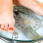 A close up of 2 feet on a pair of weighing scales.