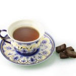 A cup of black tea and a saucer next to some dark chocolate chunks.