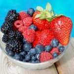 A bowl of assorted berries next to a pool.