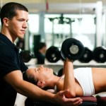 A male personal trainer spotting a female whilst performing dumbbell chest presses.