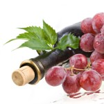 A bottle of red wine surrounded by red grapes.