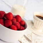 A bowl of strawberries, a jug of cream and a cup of black coffee.