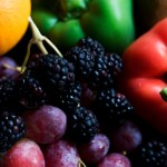 A close up shot of grapes, peppers and raspberries.