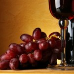 A bunch of red grapes next to a glass and bottle of red wine.