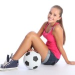 A teenage girl sitting next to a soccer ball on a white background.