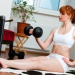 A woman lifting weights in front of the TV.