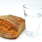 A loaf of wholegrain bread next to a glass of water.