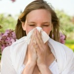 A woman in a field on a summer day, sneezing into a handkerchief.