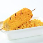 A bowl of corn topped with one piece of corn on the cob.