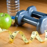 A selection of apples, dumbbells, water and a tape measure.