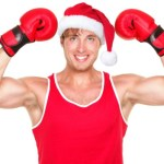 A man in a Santa hat flexing his muscles and wearing boxing gloves.