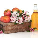 A glass bottle of cider next to a wooden crate of apples and flowers.