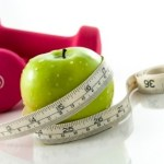 A green apple wrapped in a tape measure next to a pair of pink dumbbells.