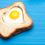 A heart shaped egg within a slice of toast.