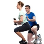 A woman performing dumbbell squats with her personal trainer.