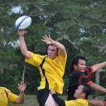 A man catching a rugby ball during a game.